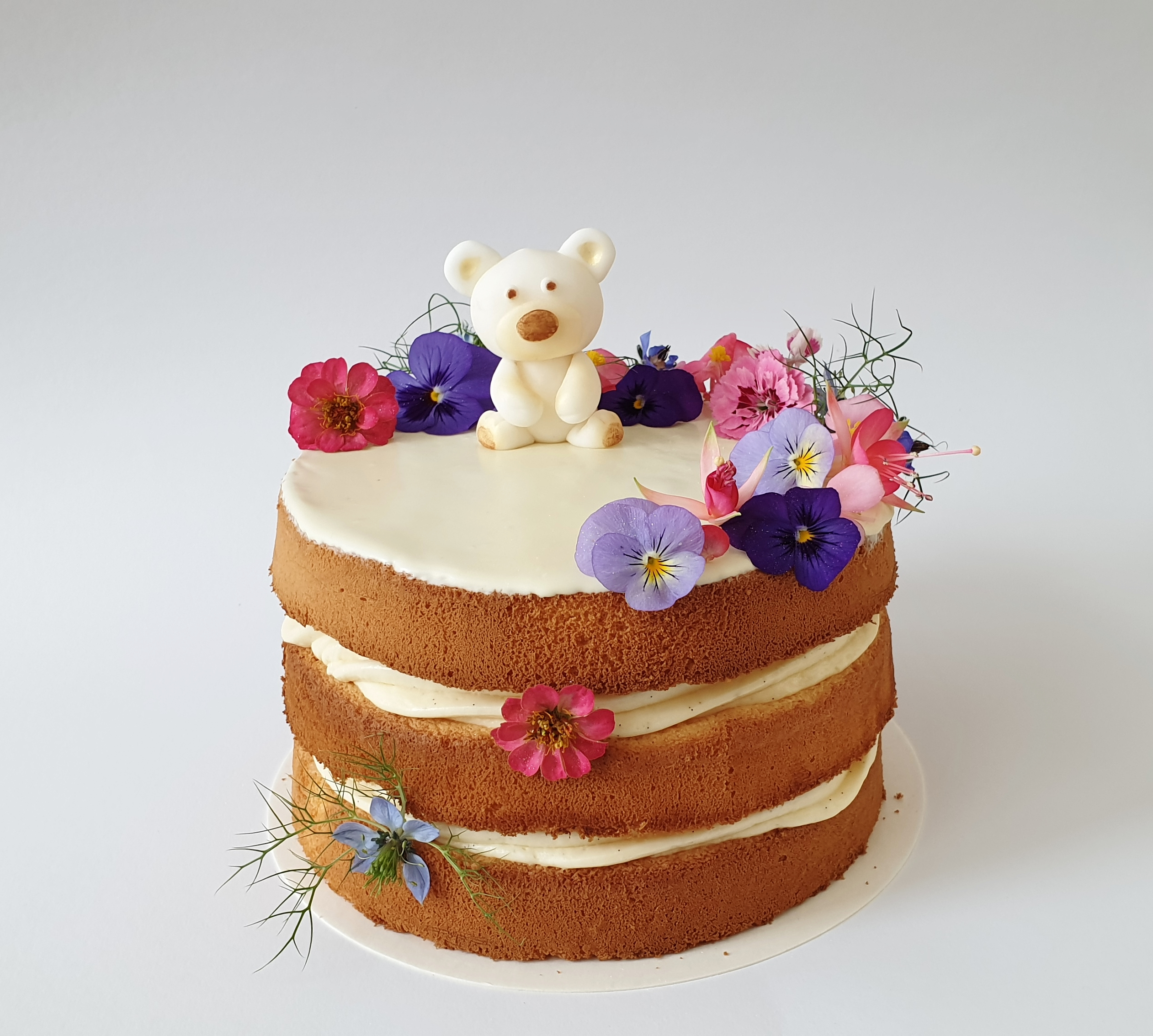 naked cake with edible flowers and fondant teddy bear